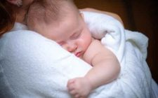 baby sleep on hands of mother