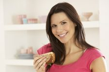Pregnant Woman Making Sandwich In Kitchen At Home